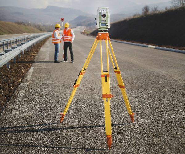 Survey tripod in foreground with workers discussing something in background